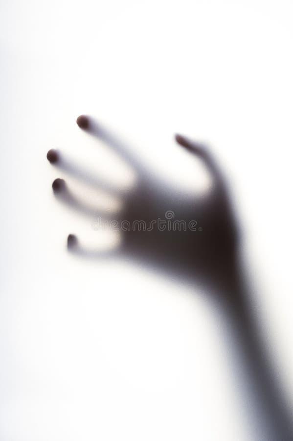 Ombre diffuse de main avec les doigts minces derrière le verre givré photos libres de droits