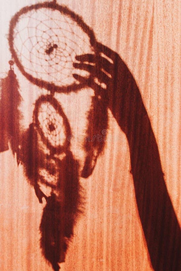 Ombre du dreamcatcher et des mains faits main image libre de droits