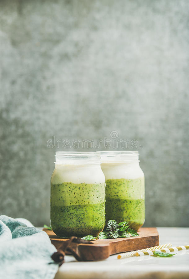Ombre layered green smoothies with fresh mint in glass jars stock photos