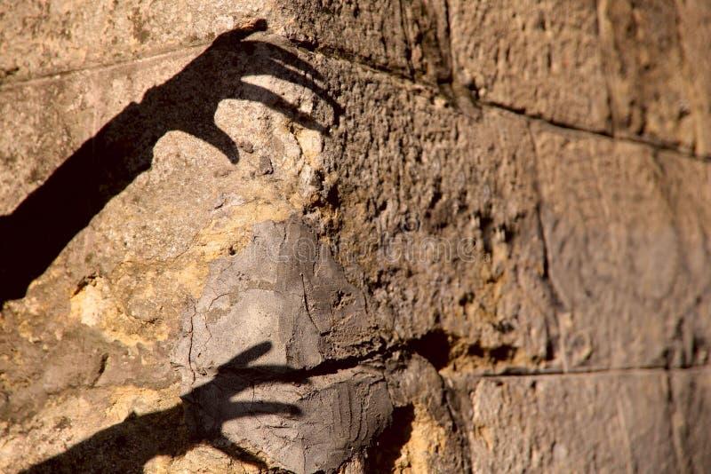 Ombre noire étrange de silhouette de deux mains sur un vieux mur en pierre brun image stock