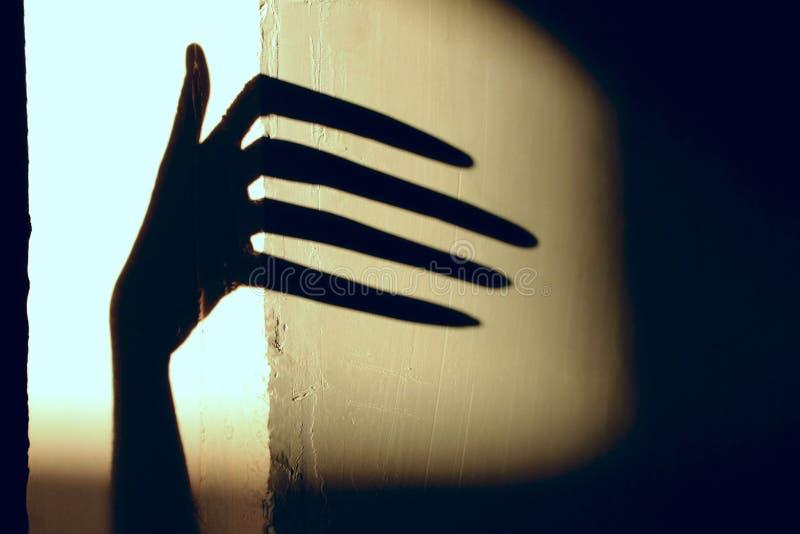 Ombre noire d'une grande main sur le mur images libres de droits