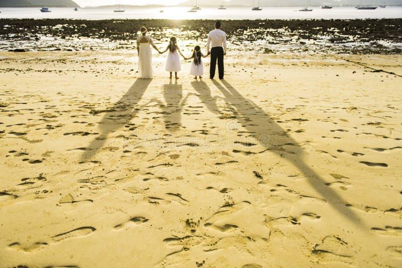 Ombre sur la plage du regard de famille vers la mer dans le jour du mariage Copie de pied photographie stock libre de droits