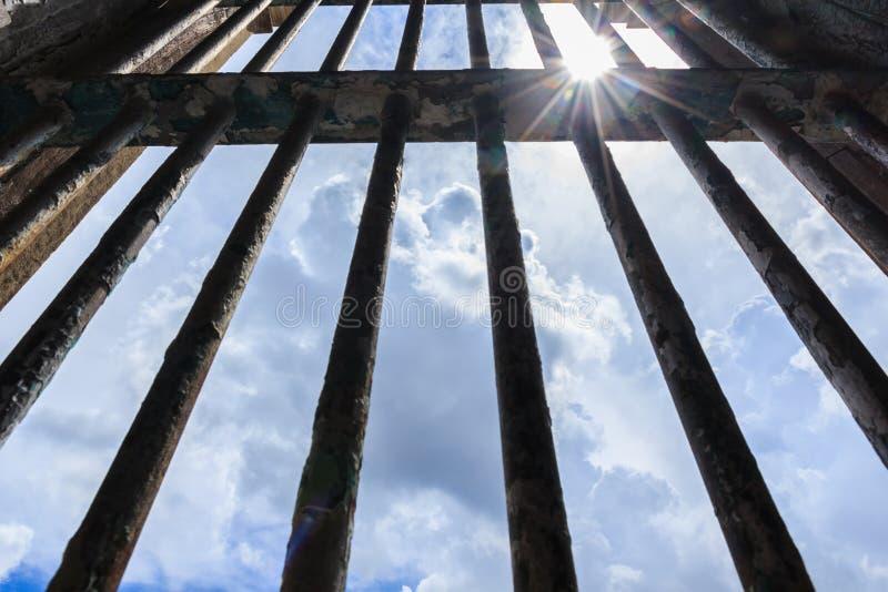 Ombreggi splendere attraverso le barre di vecchia prigione fotografia stock