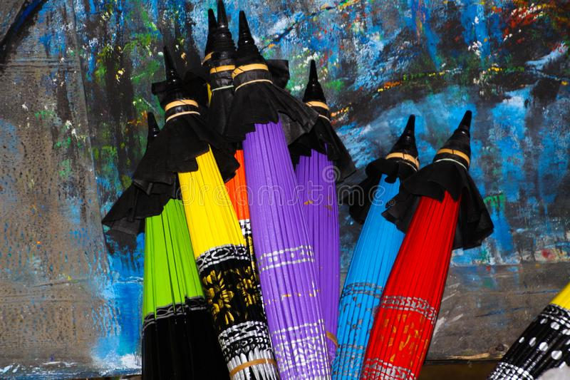 Ombrelli di carta variopinti piegati che pendono ad una parete dipinta in Chiang Mai, Tailandia illustrazione vettoriale