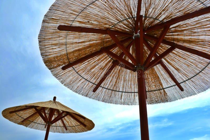 Ombrelli di spiaggia di Reed con il cielo blu e le nuvole immagini stock libere da diritti