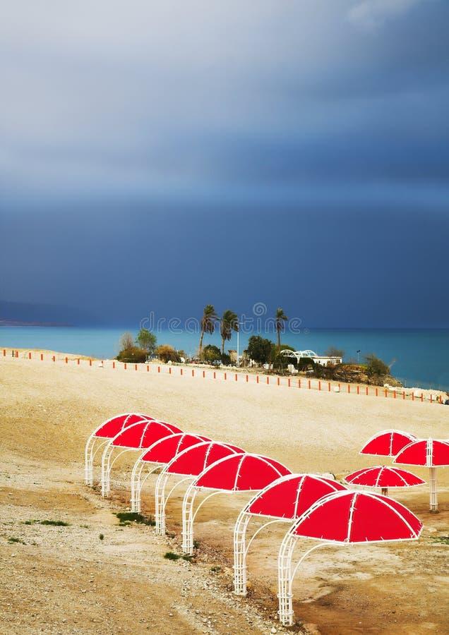 Ombrelli di spiaggia rossi sul litorale del mare guasto immagini stock libere da diritti