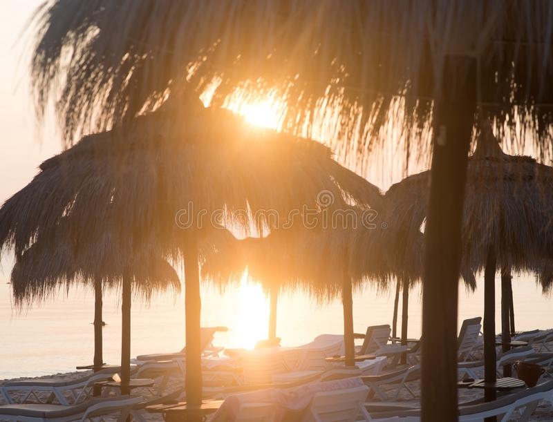 Ombrelli di Tiki Hut Vista dell'alba sulla spiaggia in Tunisia fotografie stock