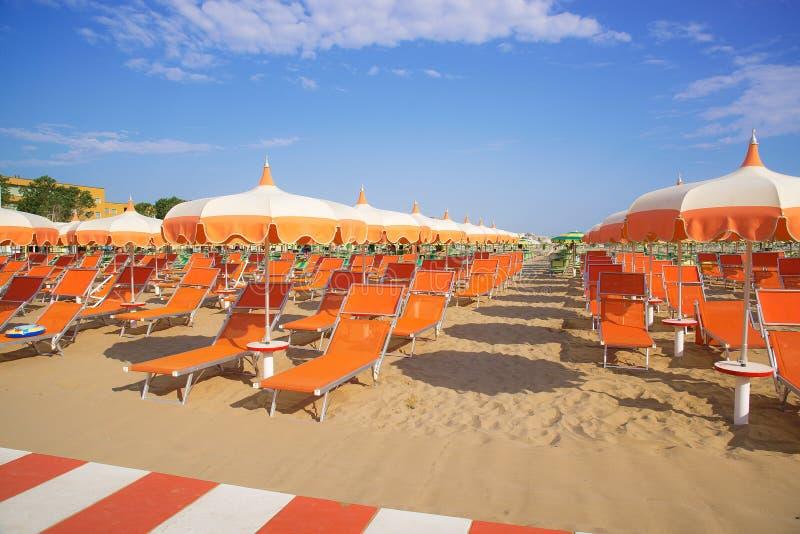 Ombrelli e chaise longue arancio sulla spiaggia di Rimini in  immagini stock libere da diritti