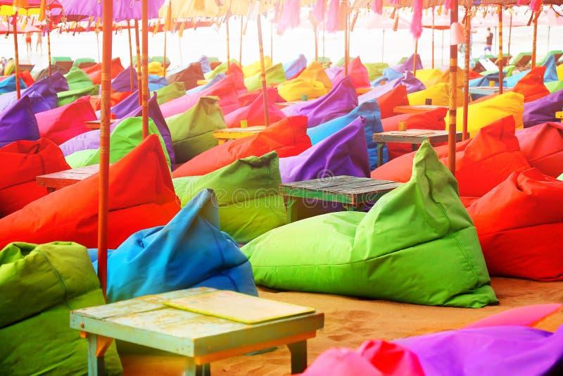 Ombrelli, ottomani e tavole di spiaggia luminosi multicolori nel caffè della spiaggia Fondo multicolore di estate immagini stock libere da diritti