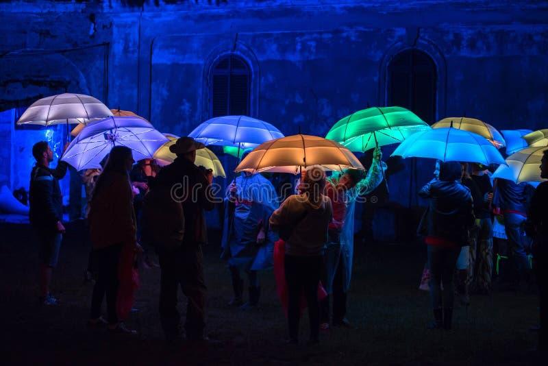 Ombrelli variopinti illuminati dalle lampade principali nella notte fotografie stock
