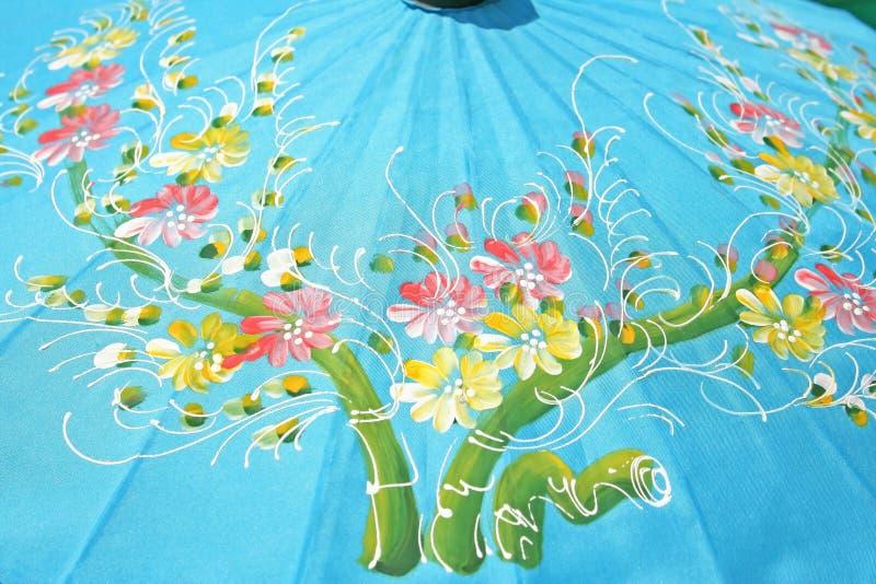 Ombrello blu con i fiori su fondo, ombrello di struttura fatto dalla carta del gelso, fatta a mano immagini stock