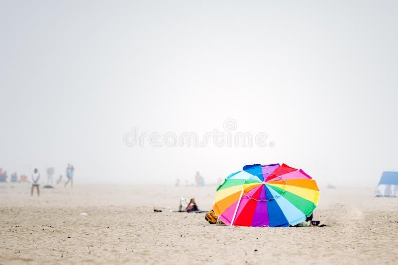 Ombrello dell'arcobaleno su una spiaggia nebbiosa immagine stock libera da diritti