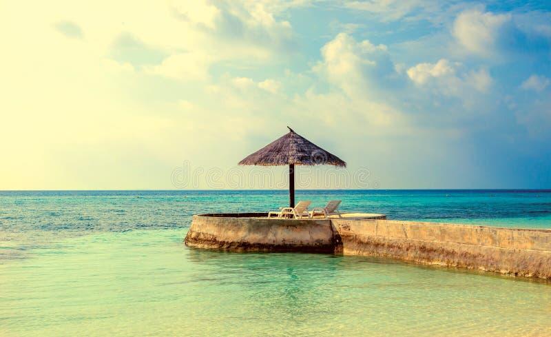 Ombrello della palma ai precedenti dell'acqua azzurrata e del tramonto stupefacente, Maldive immagini stock