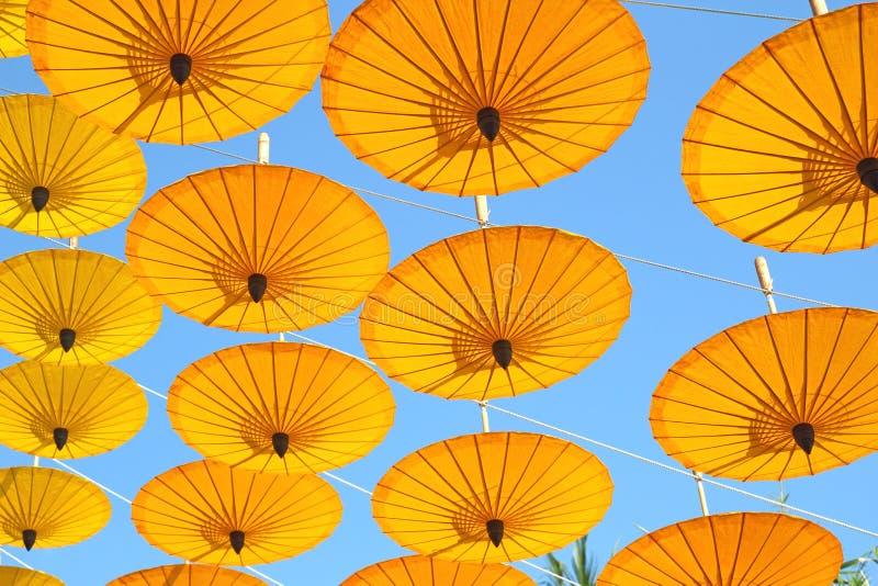 Ombrello di carta giallo che galleggia nel cielo blu fotografia stock