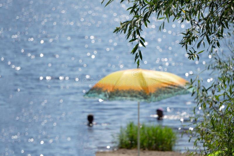 Ombrello di foglia di palma naturale tropicale e chaise longue di legno sulla spiaggia sotto l'ombra dei cocchi che trascura la s fotografia stock
