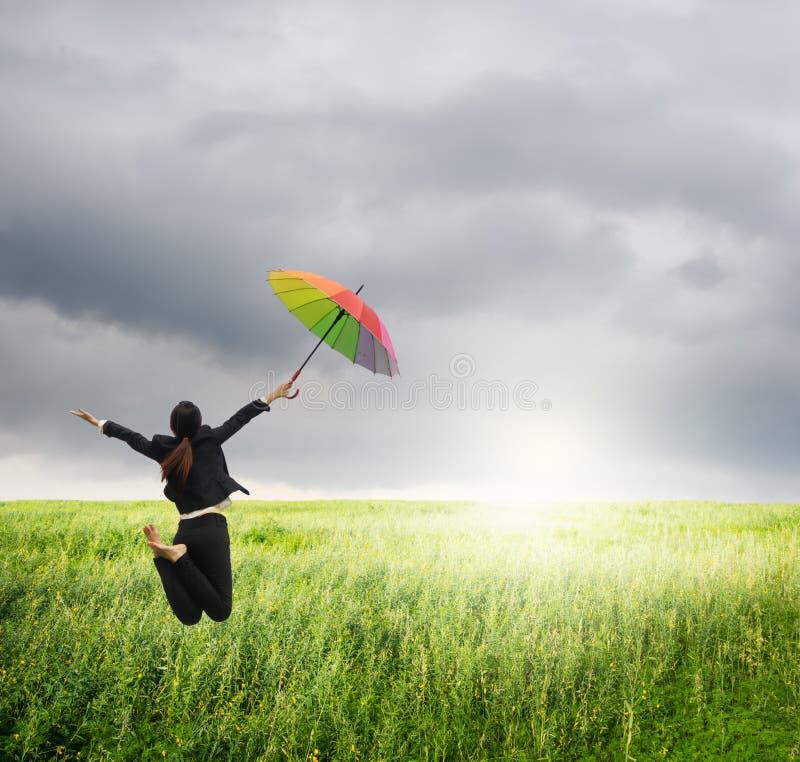Ombrello di salto dell'arcobaleno della tenuta della donna di affari nelle risaie e nel raincloud verdi fotografia stock libera da diritti
