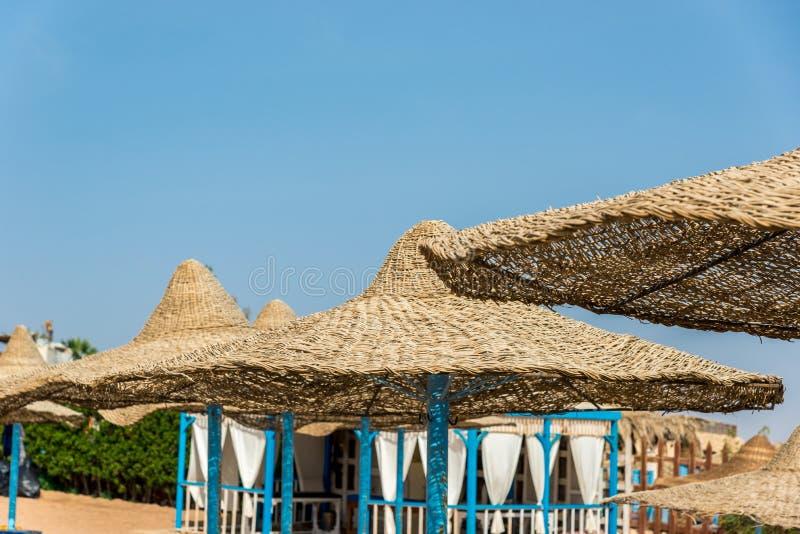 Ombrello di sole di vimini solo alla spiaggia mediterranea dal mare Parasoli e parasole di bambù naturali dell'ombrello di estate fotografia stock libera da diritti