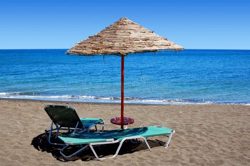 Ombrello di spiaggia nero in Grecia immagine stock libera da diritti