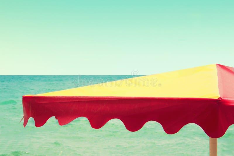 Ombrello di spiaggia sui precedenti del mare, retro stile d'annata fotografia stock libera da diritti