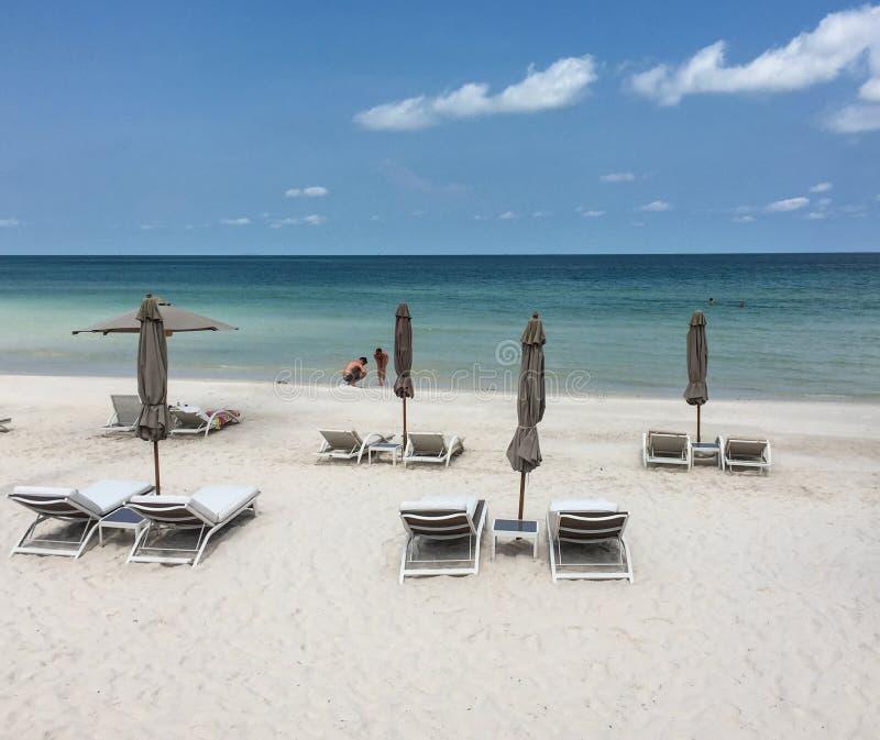 Ombrello e sdrai della capanna sulla spiaggia sabbiosa vicino al Se blu immagini stock