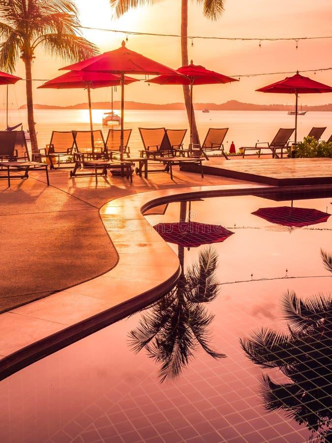 Ombrello e sedia intorno alla piscina all'aperto in hotel e nella ricerca immagine stock libera da diritti