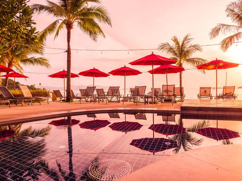 Ombrello e sedia intorno alla piscina all'aperto in hotel e nella ricerca immagini stock