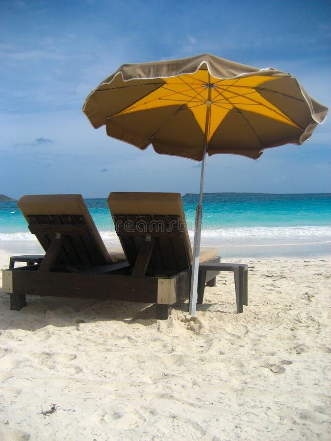 Ombrello e sedie di spiaggia di rilassamento a St Martin fotografie stock