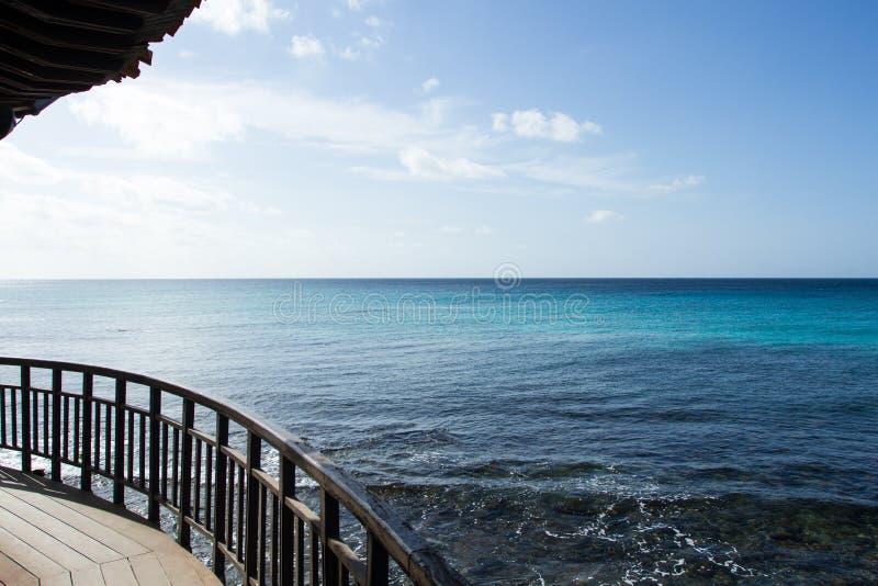 Ombrello, inferriata e l'Oceano Atlantico della paglia fotografie stock libere da diritti