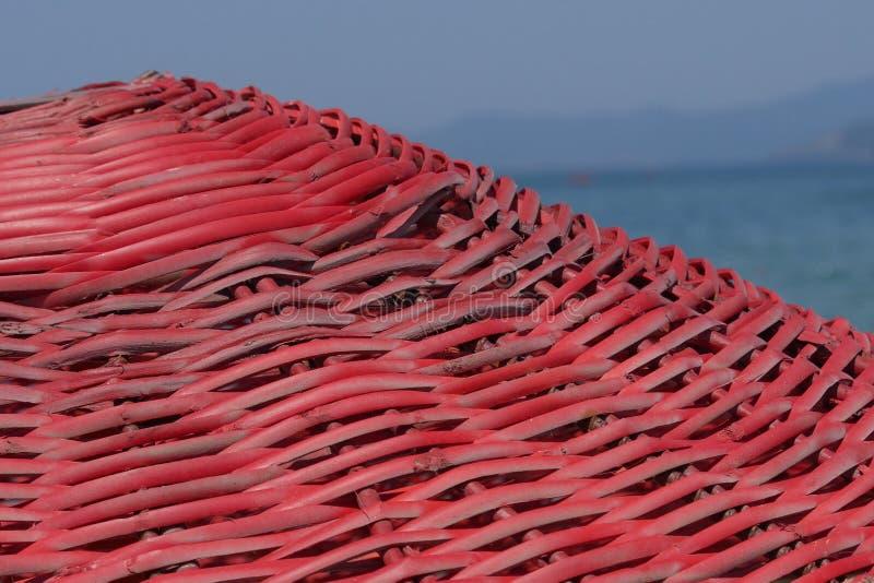 Ombrello rosso contro lo sfondo del mare sulla spiaggia di mattina fotografia stock libera da diritti