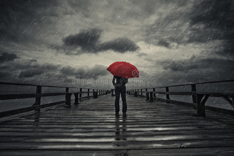 Ombrello rosso in tempesta fotografia stock