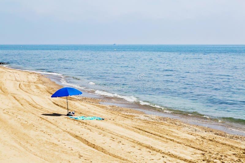 Ombrello solo sulla spiaggia fotografia stock