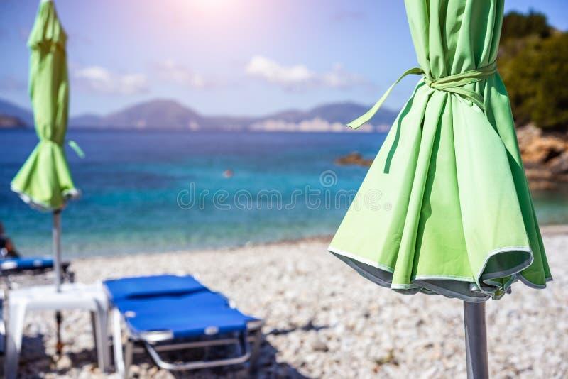 Ombrello verde di lettino sulla spiaggia bianca dello stoe dalle chiare acque blu del turchese del mar Mediterraneo il giorno di  fotografia stock