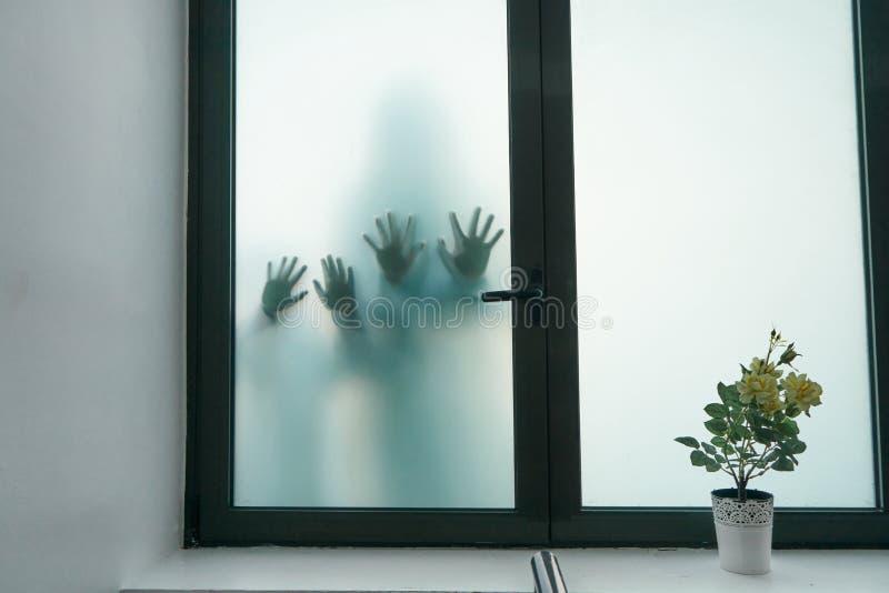 Ombres brouill?es de deux enfants d'horreur Les mains sur le verre Personnes dangereuses derri?re le verre givr? Personnes de mys photographie stock