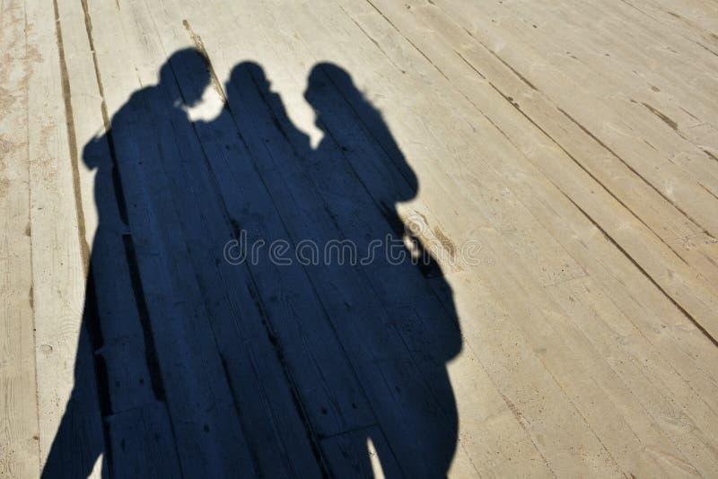 Ombres d'une famille faisant le selfie sur le plancher de bois de construction images stock
