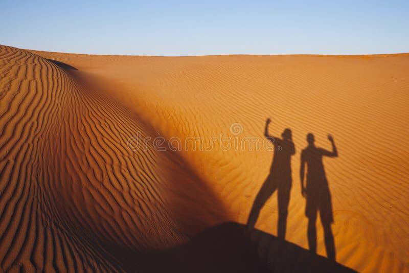 Ombres de deux amis sur la dune de sable photos stock