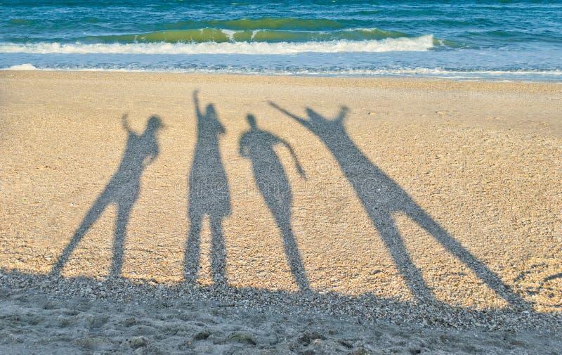 Ombres de quatre personnes dans la perspective de la mer et du ciel photos libres de droits