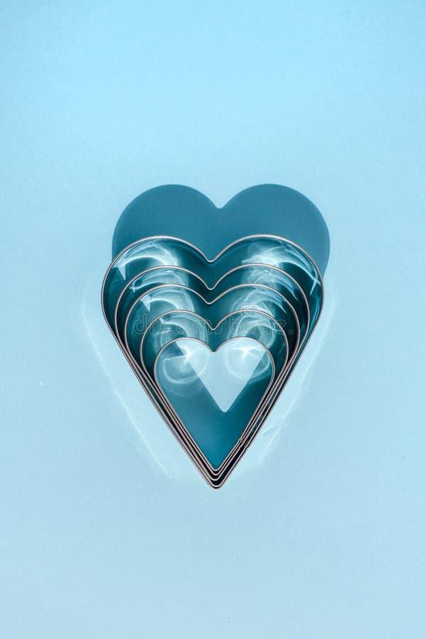 Ombres des formes en métal sous forme de coeur sur le bleu image libre de droits