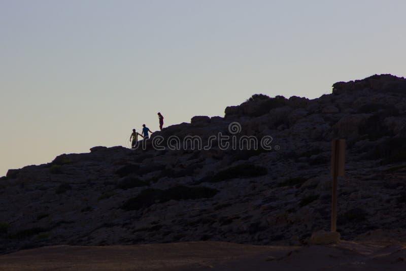 Ombres des personnes s'accrochant à la roche dans la lumière arrière image libre de droits