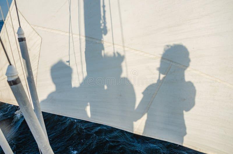 Ombres des plaisanciers et des passagers d'un bateau à voile sur une voile photo stock