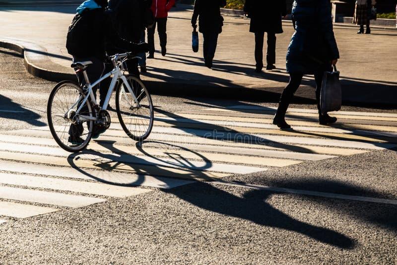 Ombres et silhouettes des personnes traversant la rue de ville photographie stock libre de droits