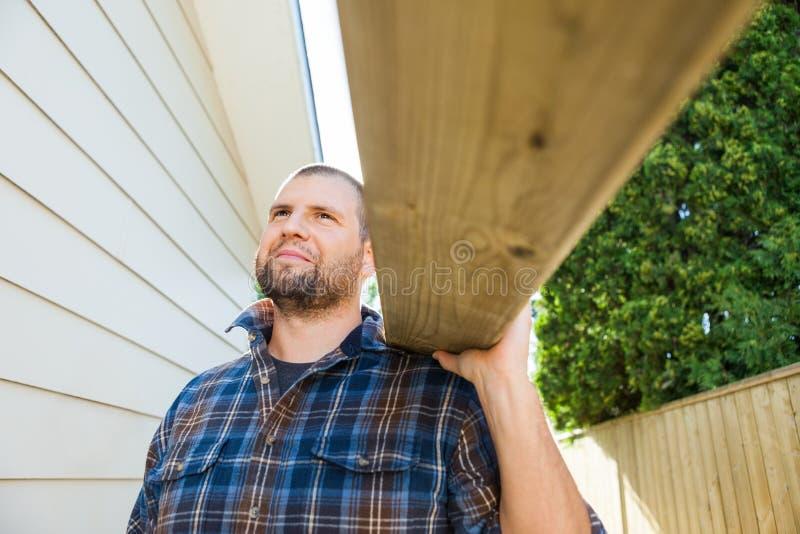 Ombro de Carrying Plank On do carpinteiro em imagens de stock royalty free