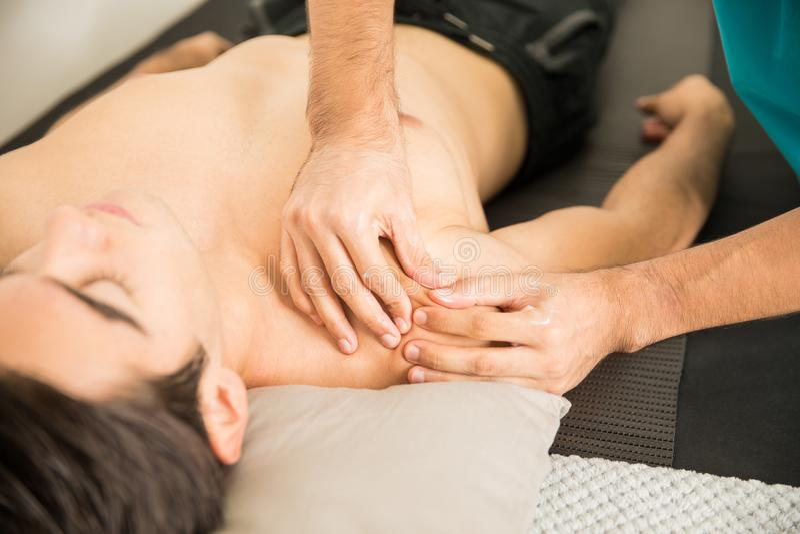 Ombro do ` s de Massaging Man do terapeuta na clínica imagens de stock
