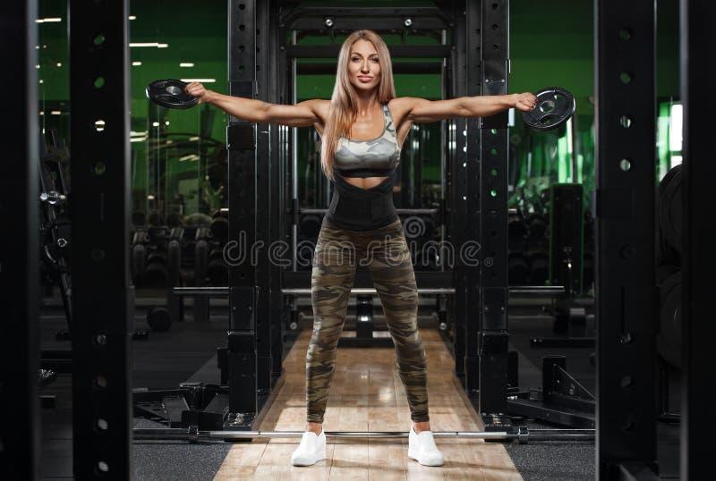 Ombros atléticos do treinamento da menina no gym, dando certo Exercício da mulher da aptidão foto de stock royalty free