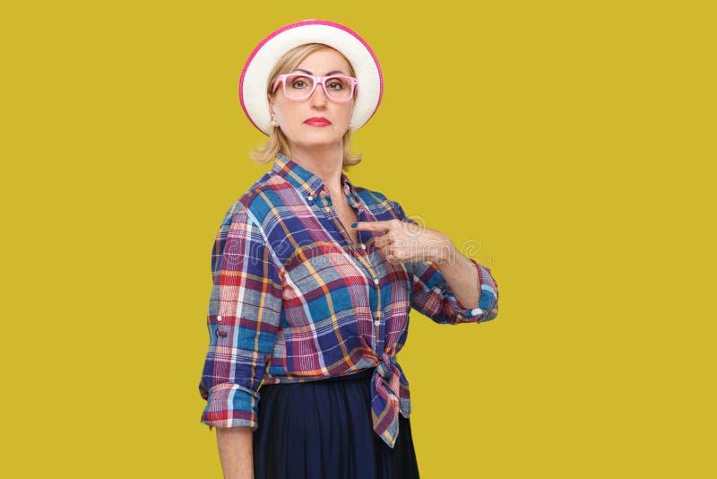 Omdat ik ben Portret van trotse ernstige moderne modieuze rijpe vrouw in toevallige stijl met hoed en oogglazen die, het richten  stock foto's