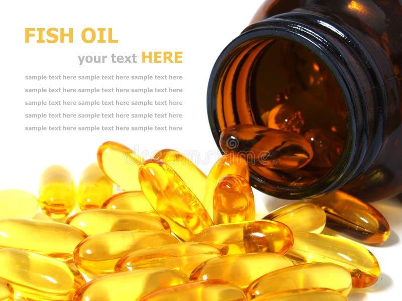 Omega 3 cápsulas del aceite de pescado que se derraman fuera de una botella fotos de archivo libres de regalías