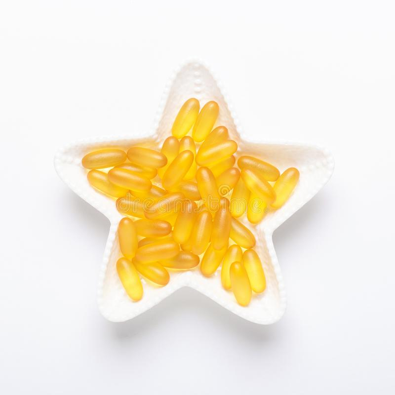Omega 3 capsules in star shape plate on white background Fish oil Yellow softgels Vitamin D, E, A supplement royalty free stock photo