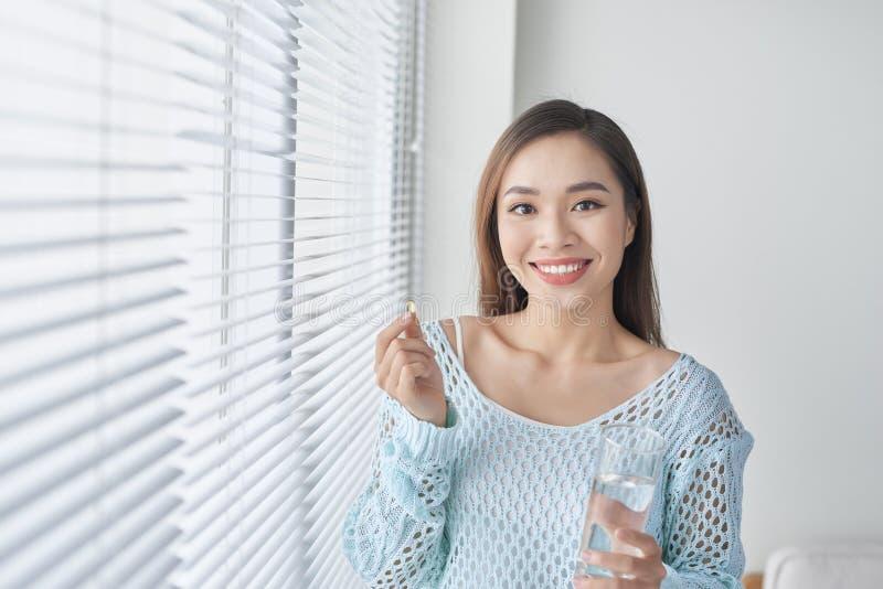 Omega 3. Fat fish. Beautiful girl takes fish oil. Woman takes omega 3. Healthy food. Vitamin D, E, fish oil capsules.  royalty free stock photo