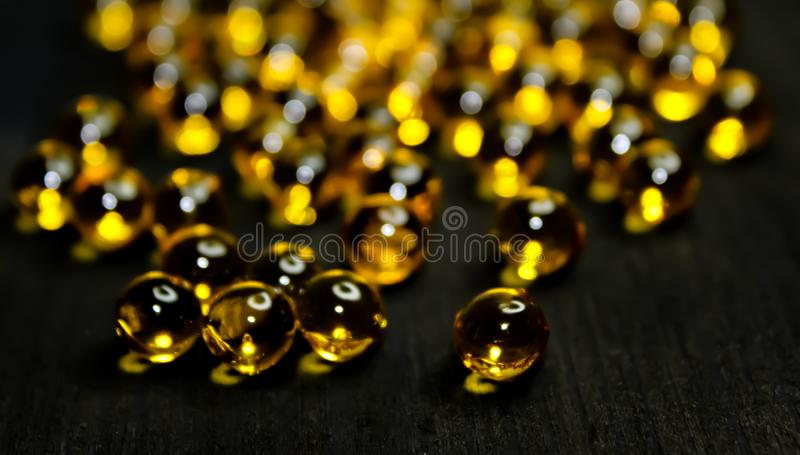Omega 3-6-9 fish oil yellow round capsule round pills, linseed oil on wooden black background. stock photography