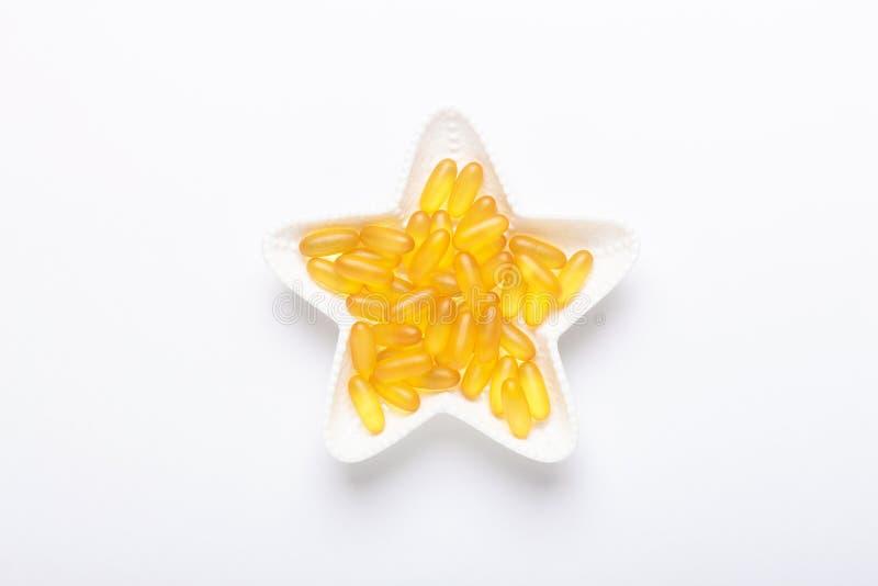 Omega 3 kapsuły w gwiazdowym kształta talerzu na biały tło Rybiego oleju softgels witaminy Żółty d, E, A nadprogram zdjęcie royalty free