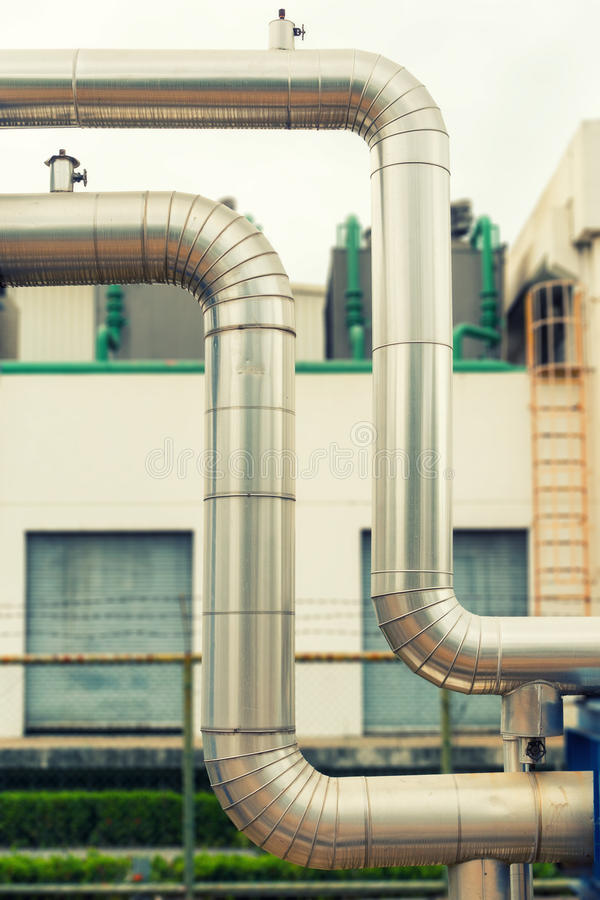 Omega loop steam pipeline on cooling tower background. stock image